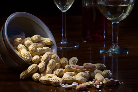 closing time: peanuts in a ceramic bowl and on a dark wooden table, wine glasses in the background, evening scene at home