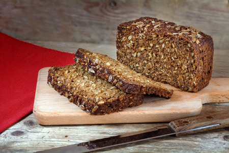 fresh dark rye bread with whole grain and sunflower seeds on a rustic wooden board Stok Fotoğraf