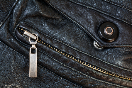 stud: zipper and press stud in old black leather, close up