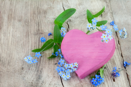 pink heart shape made of wood with forget-me-not flowers on a rustic wooden background, copy space for your text photo