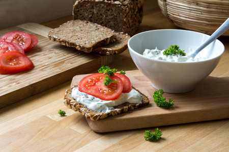 natural: fresh curd cheese dip with herbs in a white bowl and rustic wholegrain bread with tomatoes on a kitchen board, healthy and powerful meal with natural food products Stock Photo