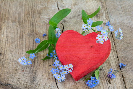 red heart shape made of wood with forget-me-not flowers on a rustic wooden background with copy space photo