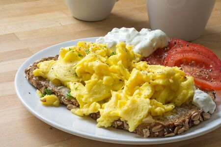 scramble: scrambled eggs on rustic bread with tomatoes and curd cheese cream Stock Photo