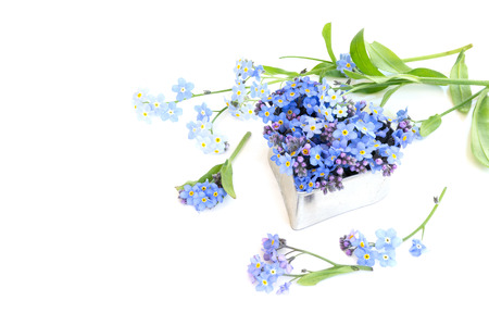 silver heart shape with forget-me-not flowers isolated on a white background, copy space for your text photo