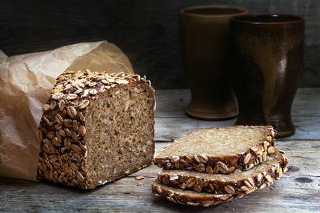 volkoren roggebrood met zaden op een verweerde houten plank, rustiek aardewerk in de donkere achtergrond Stockfoto