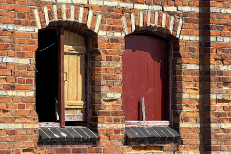 boarded up: boarded up windows in an old wall of an obsolete brick biulding