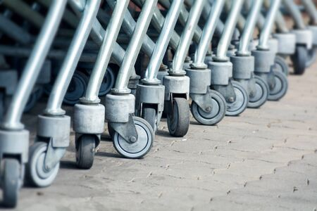wheels of shopping carts in a diagonal row, details with selected focus photo