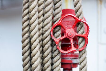 industrie: red wheel of a stop valve and ropes on a Tall Ship