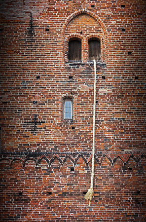 Rapunzel Fairy Tale, a long blond hair plait hanging out of the window of an old brick tower Stock Photo