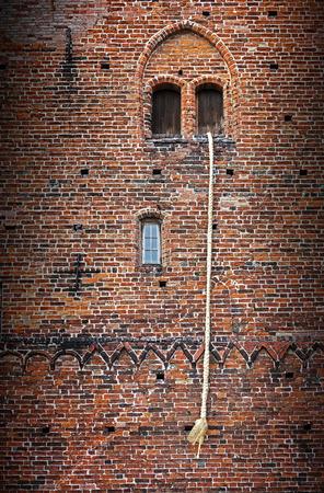 Rapunzel Märchen, eine lange blonde Haare Zopf aus dem Fenster eines alten Backstein-Turm hängen