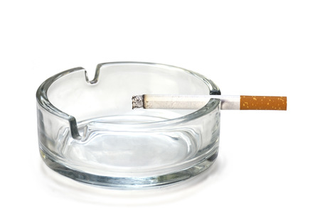ciggy: filter cigarette in an ashtray made of glass, isolated on a white background