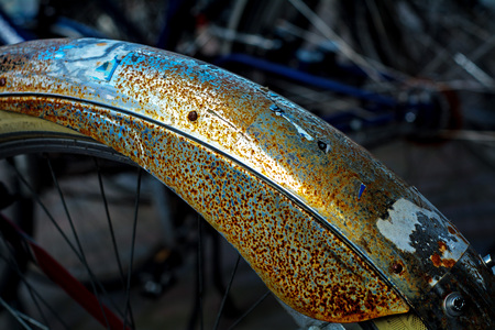 transience: rust and remnants of stickers on a bicycle mudguard, abstract dark background with bright diagonal, detail with narrow depth of field