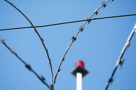 emergency light: barbed wire and blurred red emergency light in the background against the blue sky, selected focus, narrow depth of field