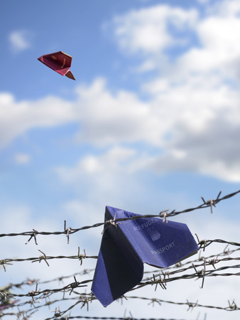 crisis: two passports folded as paper planes, the European one is flying in the blue sky, the other one is labeled with refugee and remains trapped in the barbed wire of the frontier, copy space