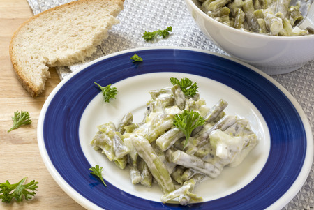 cream and green: salad of green beans with sour cream dressing and parsley garnish on a plate, bread and bowl in the background, fresh side dish ideal for barbecue