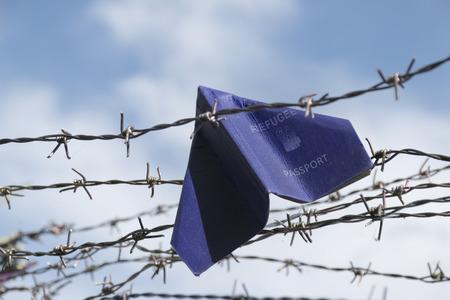 pasaporte: refugiados pasaporte etiquetada pliega como un avión de papel quede atascado en el alambre de púas de la frontera contra el cielo azul con nubes blancas, copia espacio