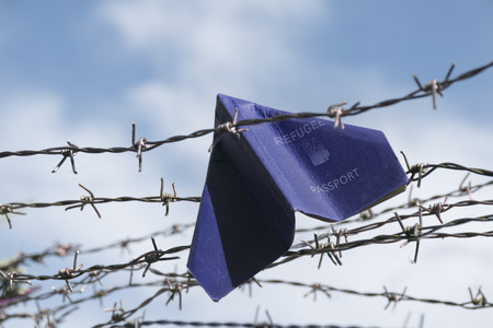 refugee labeled passport folded as a paper plane get stuck in the barbed wire of the border against the blue sky with white clouds, copy space