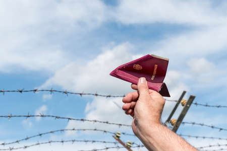 iron fence: mans hand holding a German passport as a paper airplane  over a  barbed wire fence against the blue sky, copy space
