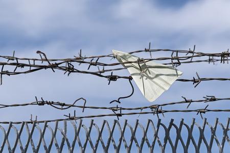Papierflugzeug eines Visums Dokuments wird in Stacheldraht, blauer Himmel und Kopie Raum stecken