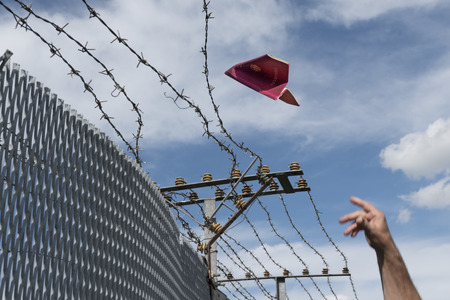 old fence: mans hand throwing his passport folded as a paper airplane over a barbed wire fence,  blue sky and copy space