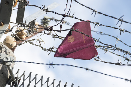 jail background: Passport folded as a paper plane hanging in the barbed wire of a border against a blue sky with clouds, copy space