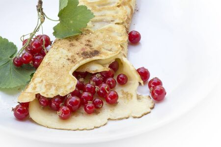 omlet: wrapped pancake or crepe with fresh red currants on a white plate as a summer dessert, copy space Stock Photo