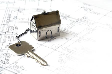 kleinen Haus-Modell aus Metall mit einem Hausschlüssel auf Architekturzeichnung gemacht, Immobilien-Konzept