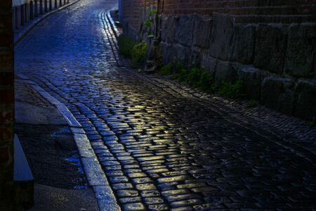 dark street: alley with wet cobblestones at night in an old town, narrow depth of field Stock Photo