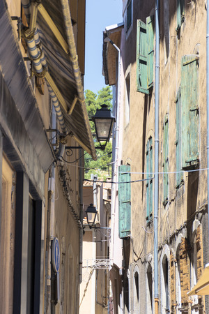 apt: Typical narrow alley with pale ocher houses and turquoise shutters in a French old town, Apt, Southern France, vertical