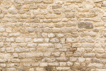 background texture, wall of pale natural stone in the old town of Apt, Southern France