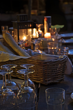 night table: prepared table for a rustic outdoor dinner at night  with wineglasses, bread and candles, vertical