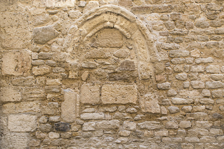 apt: background texture, wall of pale natural stone with a bricked up arch window, in the old town of Apt, Southern France