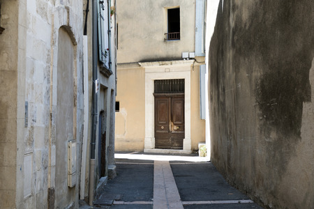 apt: narrow alley with an old wooden door in the historic center of Apt, Southern France Editorial