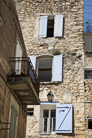 old town house: Typical old town house in south Europe built of natural stone with bright blue shutters and balconies, village of Ansouis, Provence, France, Luberon region