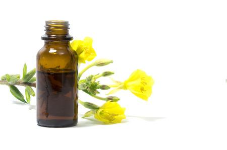 Yellow Nachtkerze (Oenothera biennis) Blumen und eine kleine Flasche mit Öl, Kosmetik und natürliche Heilmittel für empfindliche Haut und Ekzemen, isoliert auf einem weißen Hintergrund