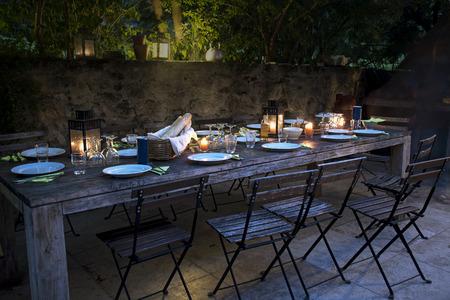 großen rustikalen Tisch auf der Terrasse für ein Abendessen mit Freunden außerhalb vom Abend vorbereitet, bis spät in die Nacht Lizenzfreie Bilder