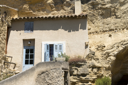 the luberon: House facade in front of a cave in the mountain in the old village of Cadenet, Provence, south France, Luberon Massif