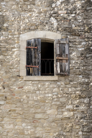 luberon: ancient building made of natural stone with a window and half-open shutters of wood, copy space in the wall, Cucuron, Provence, France, region Luberon Stock Photo