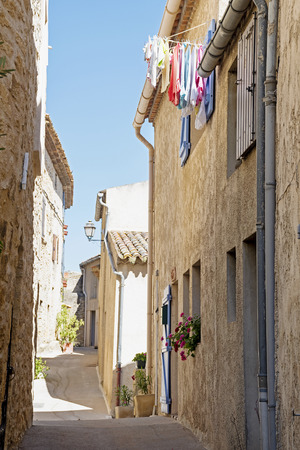 luberon: narrow street in an old mountain village in southern Europe with typical houses and colorful laundry, Ansouis, Provence, France, Luberon region Editorial