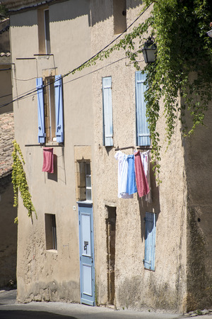 luberon: typical house in south France with blue shutters and drying laundry outside the windows in the old mountain village of Cadenet, Provence, Luberon Massif Editorial