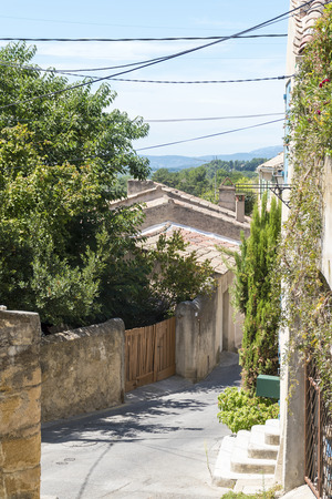 the luberon: Narrow street with typical houses, plants and current lines under the blue sky in the old mountain village of Cadenet, Provence, France, region Luberon