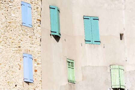 azul turqueza: fachada con persianas cerradas en azul, turquesa y verde en una antigua ciudad en el sur de Europa, Francia Editorial