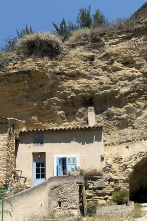 cave house: House facade in front of a cave in the mountain in the old village of Cadenet, Provence, south France, Luberon Massif, vertical