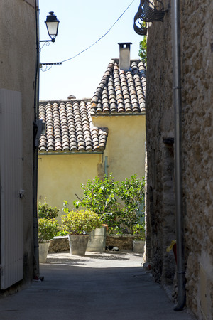 luberon: view through a narrow alleyway to a pot-garden, typical old town in southern Europe, Ansouis, Provence, France, Luberon region