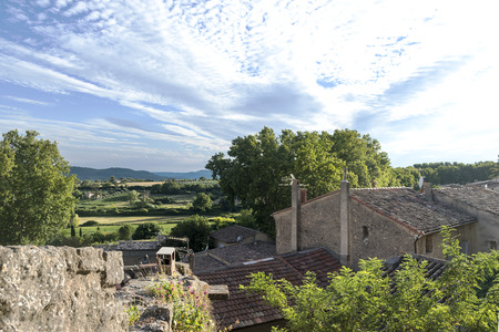 luberon: View over the roofs of a small village into the landscape of Provence against the blue sky with clouds, cucuron, France, region Luberon