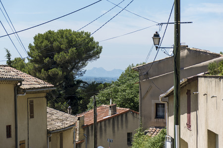 luberon: view over typical houses, plants and current lines to the mountains under the blue sky, old village of Cadenet, Provence, France, region Luberon