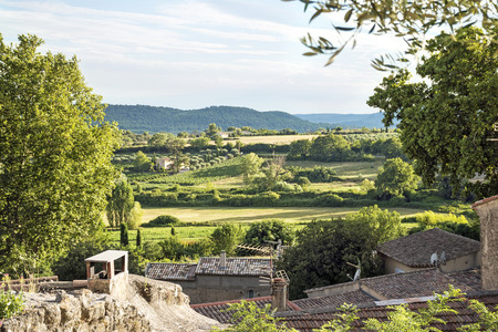 View over the roofs of an old village in the landscape of Provence, Cucuron, France, Luberon region