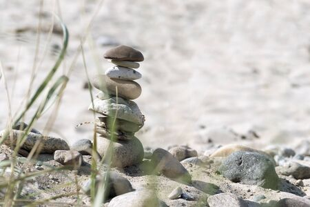 narrow depth of field: stone tower and plants on a sandy beach, vacation background with narrow depth of field