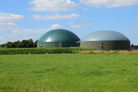 biogasinstallatie voor hernieuwbare energie op een groene weide tegen de blauwe lucht met wolken Stockfoto