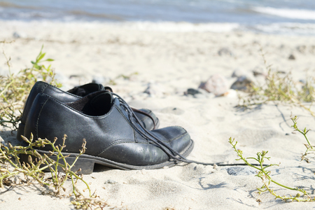 narrow depth of field: black mens shoes standing on the sandy beach, vacation background with narrow depth of field
